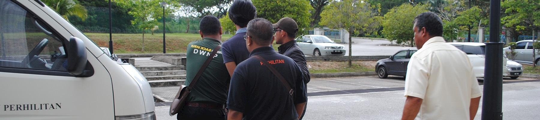 Two ex-Customs officers are escorted from court in Malaysia following sentencing for possession of protected wildlife species